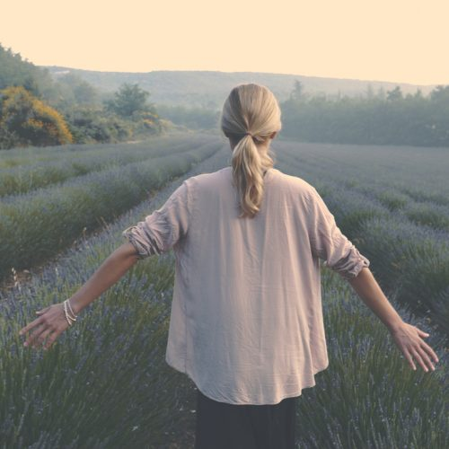 Young woman admiring lavender fields. Open arms